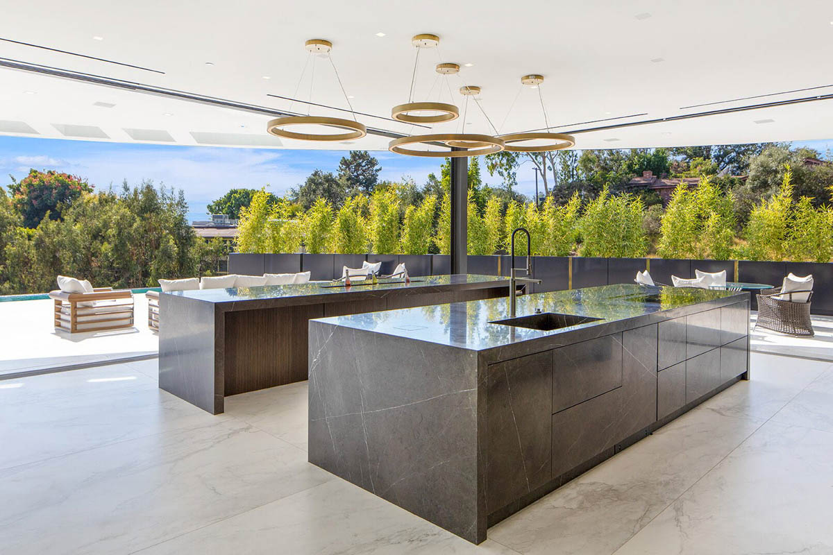 Fitucci Custom Cabinets - Los Angeles - islands built with marble and they have custom cabinets on the opposite end of the chairs. the photo is taken from the interior corner